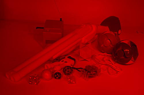 Red-lit assemblage of objects